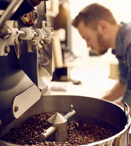 Dark and aromatic coffee beans in a modern roasting machine with the blurred image of the professional coffee roaster visible in the background